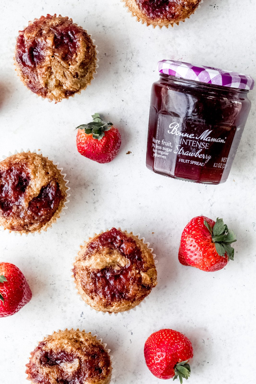 gluten free strawberry almond butter muffins next to a jar of strawberry fruit spread