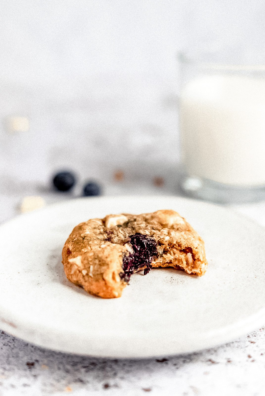 white chocolate blueberry coconut oatmeal cookie with a bite taken out