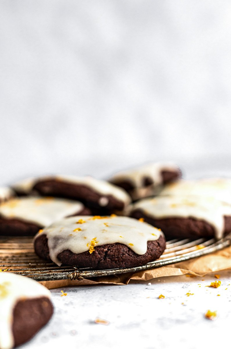 chocolate orange cookies with orange icing on a baking rack