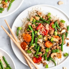 sesame chicken and green bean stir fry on a plate with chopsticks