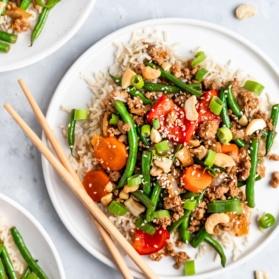 sesame chicken and green bean stir fry on a plate with chopsticks