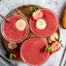 three strawberry orange banana smoothies on a wooden tray
