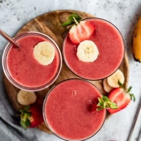 three strawberry orange banana smoothies on a wooden tray