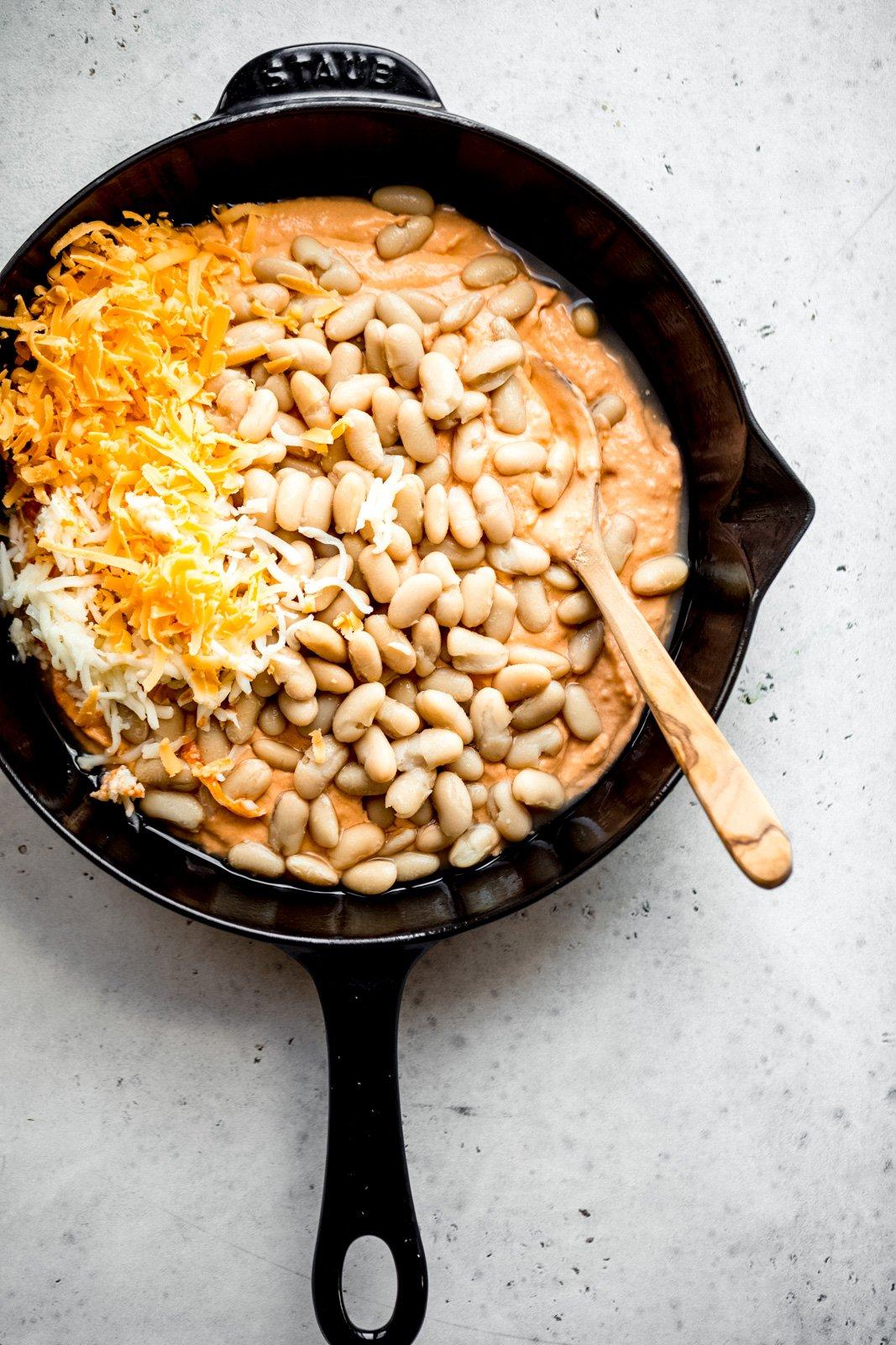 cheesy white bean buffalo dip in a skillet before baking