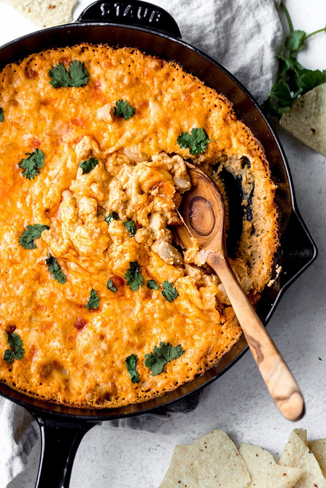 vegetarian white bean buffalo dip in a skillet with a spoon