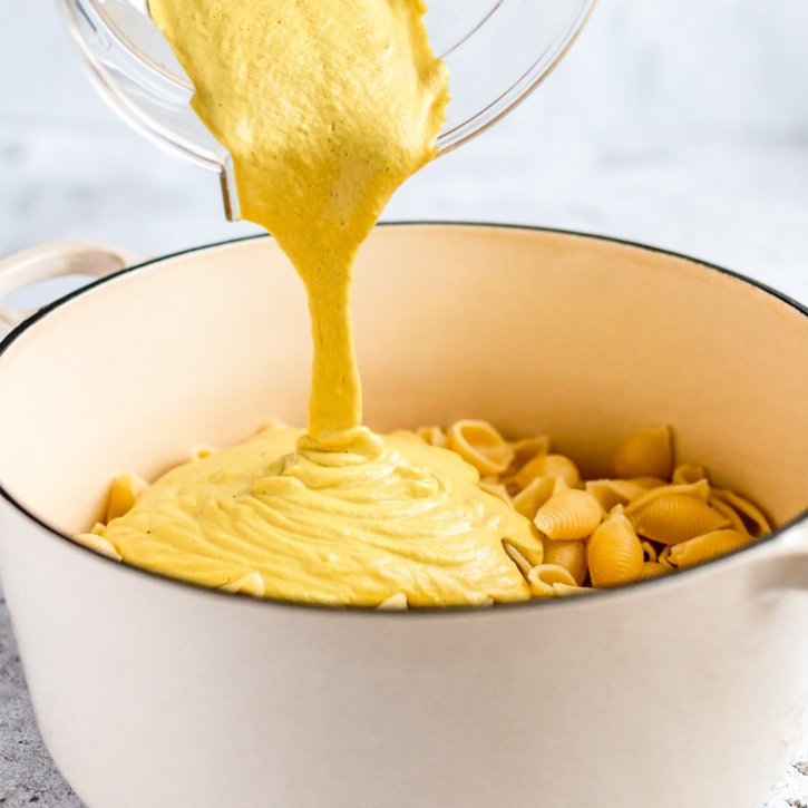 pouring vegan cashew cheese sauce into a pot of noodles