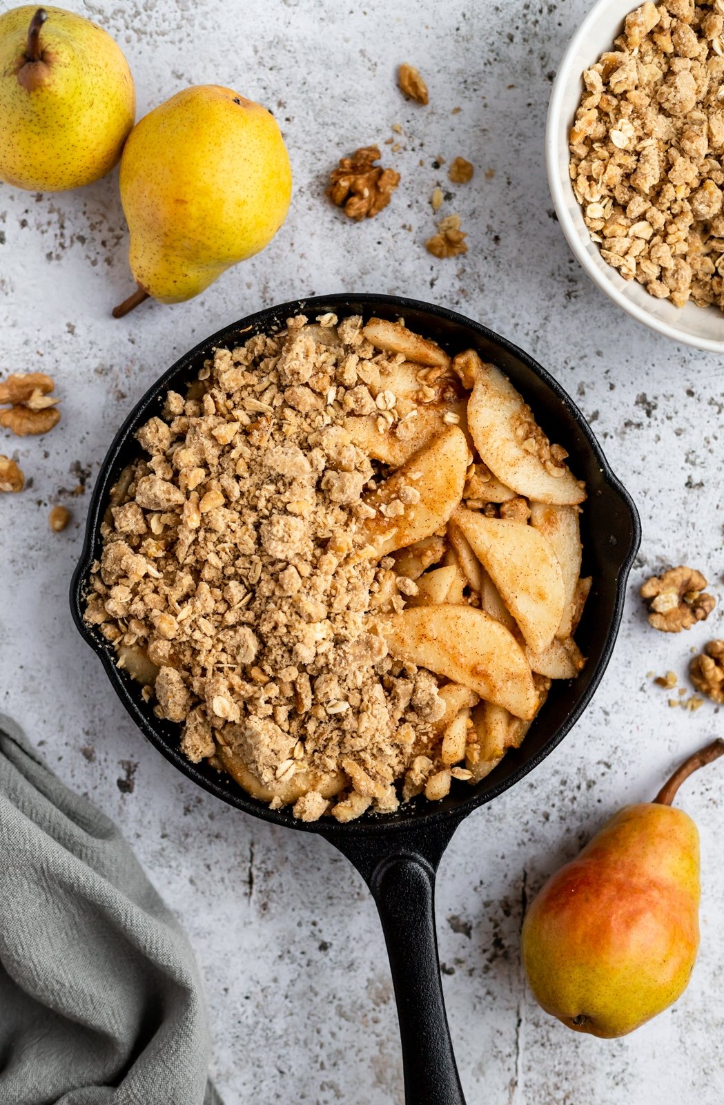 unbaked healthy pear crisp in a skillet next to pears
