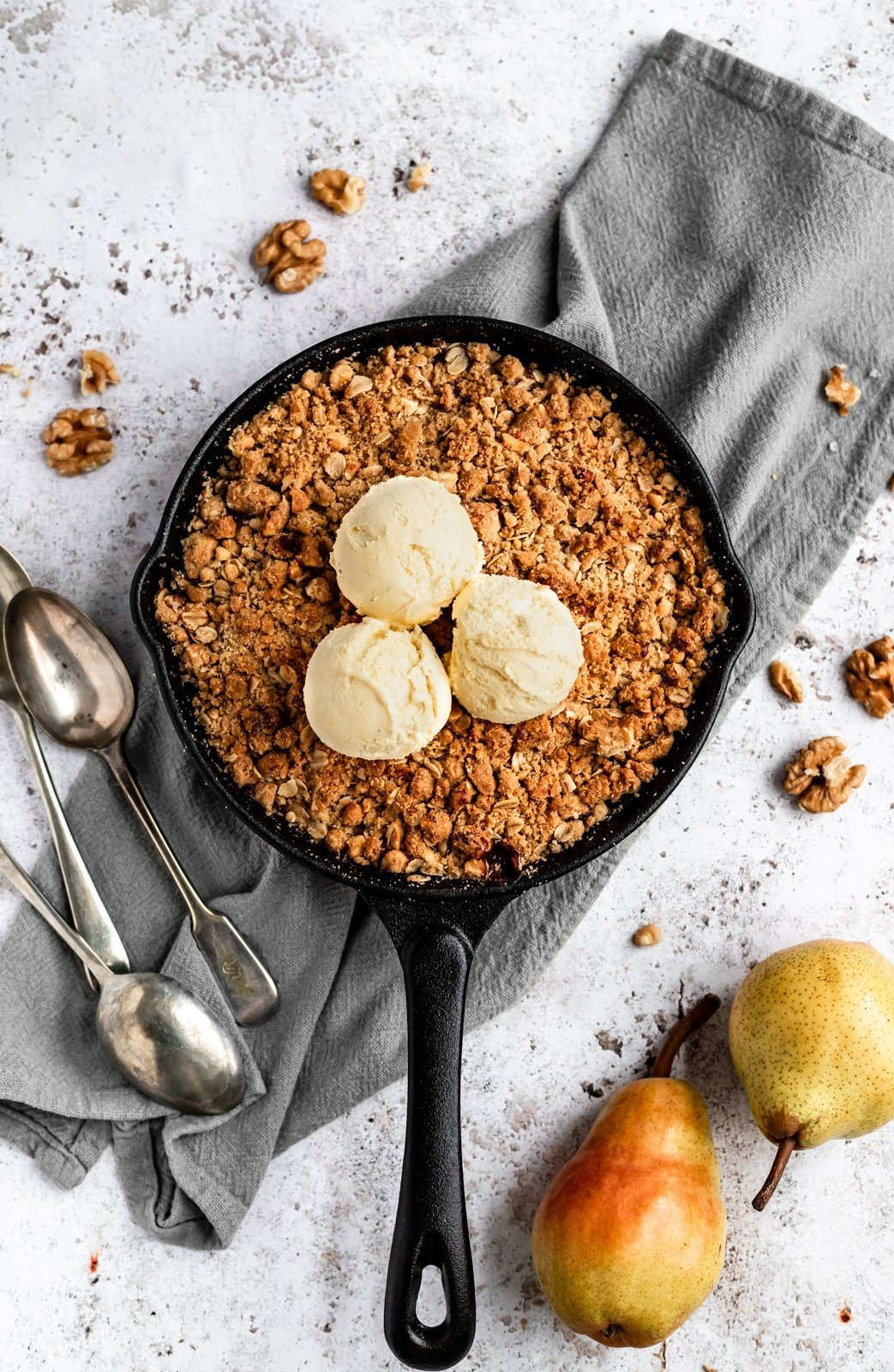 gluten free pear crisp in a skillet with ice cream scoops on top