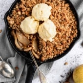 healthy pear crisp in a skillet topped with ice cream