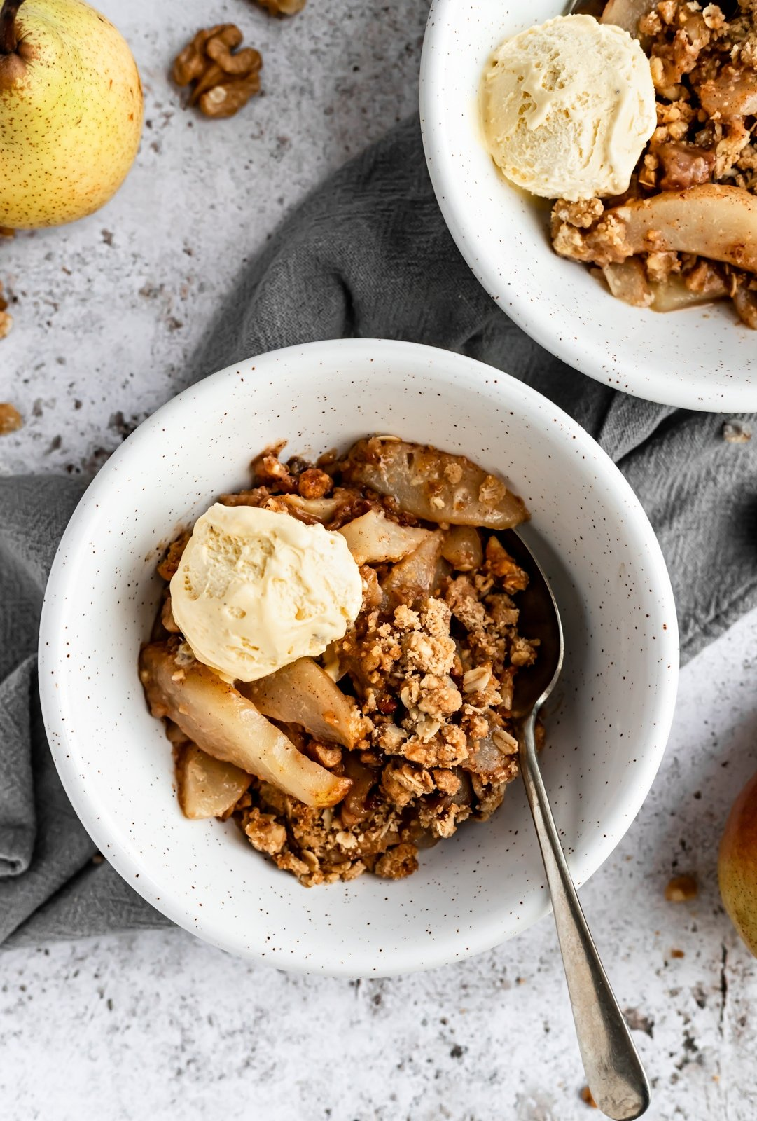 gluten free pear crisp in a bowl with ice cream