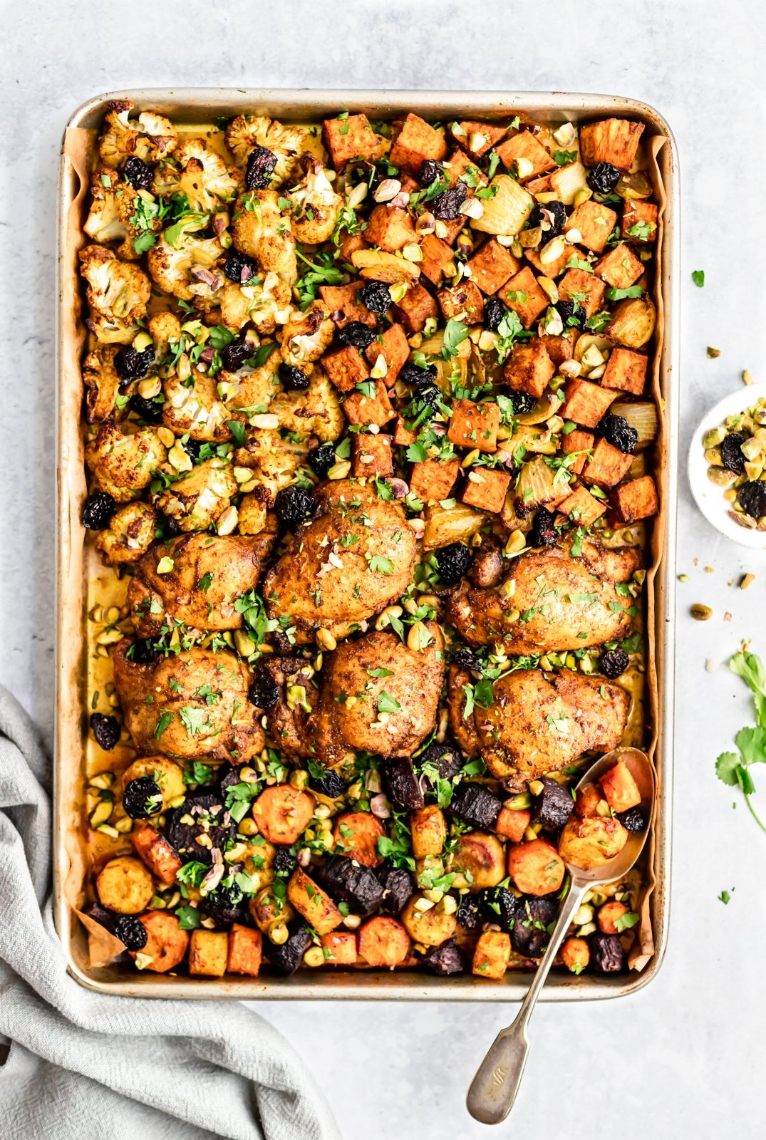 moroccan sheet pan chicken and veggies on a pan with a spoon