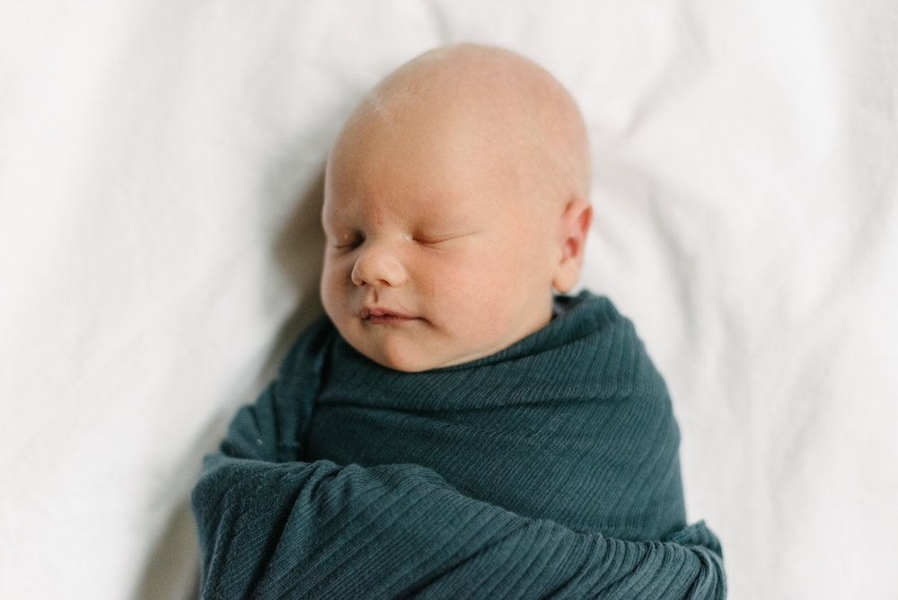 baby wrapped in a green swaddle