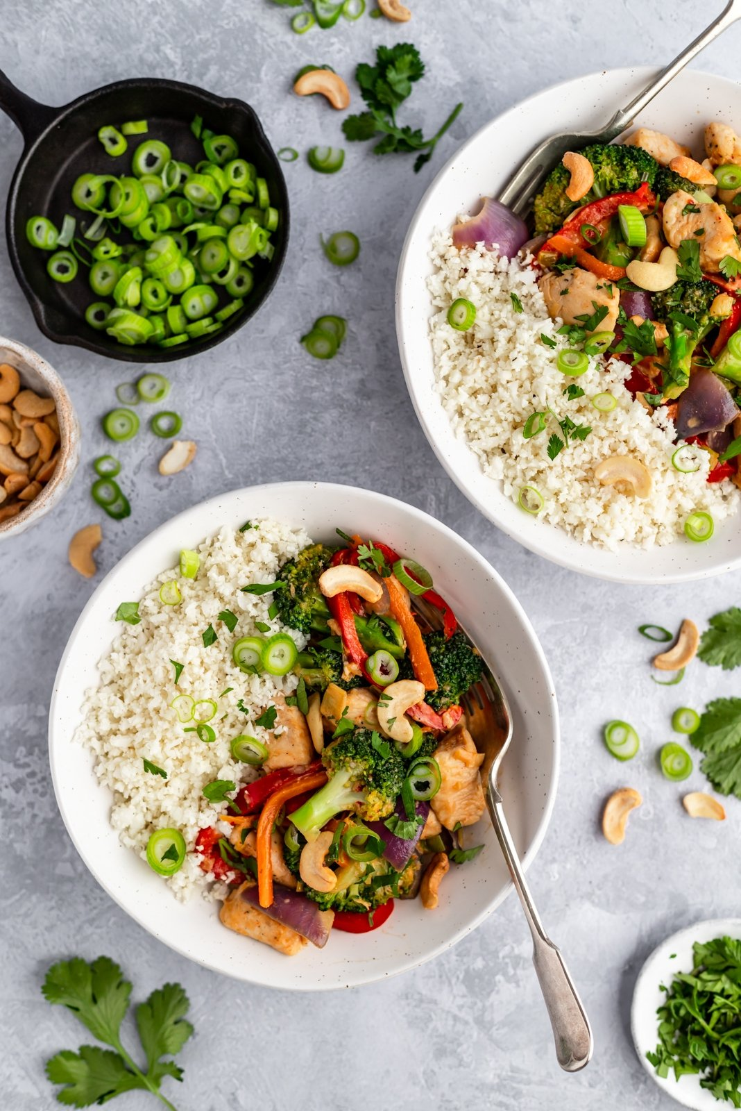 two bowls of paleo cashew chicken stir fry with coconut cauliflower rice