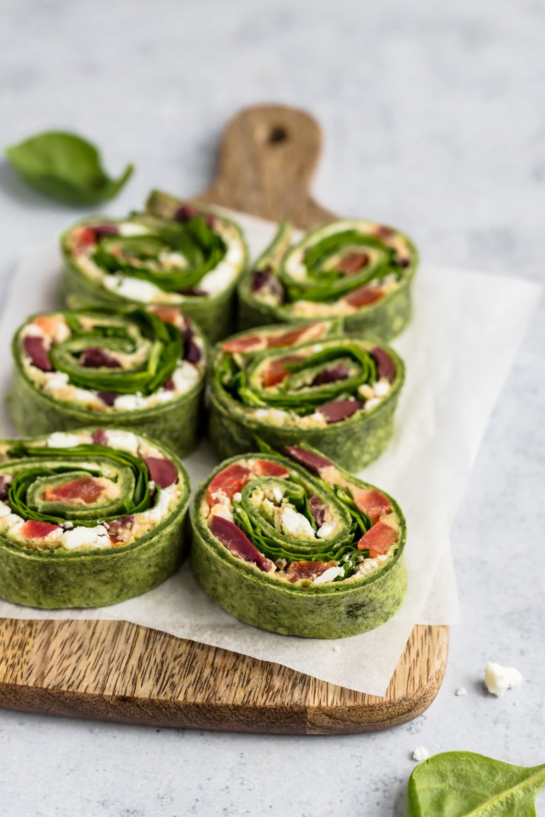 greek salad pinwheels on a wooden serving board