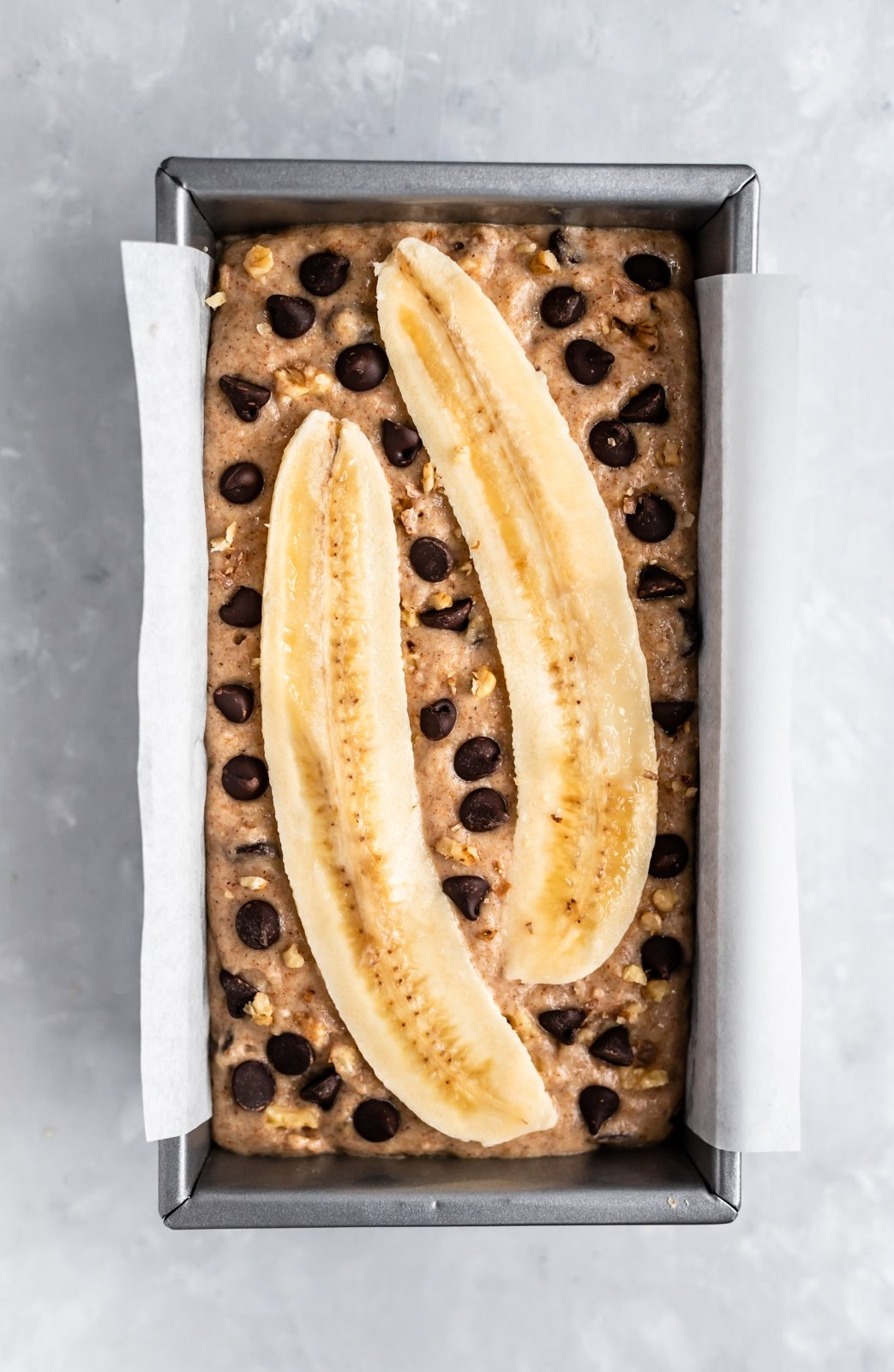banana bread in a pan before baking with two banana slices on top