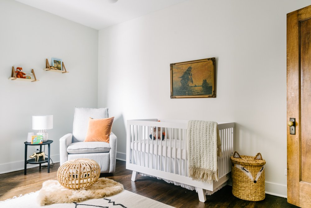nursery with a white crib and grey chair