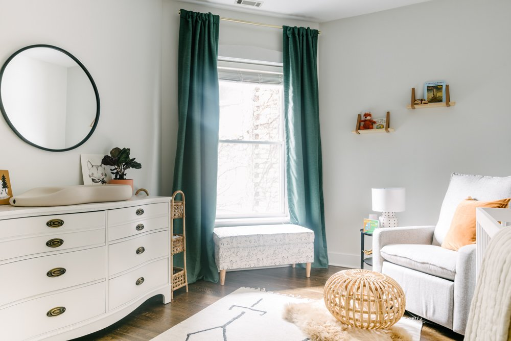 nursery room with drawers, green curtains and a grey chair