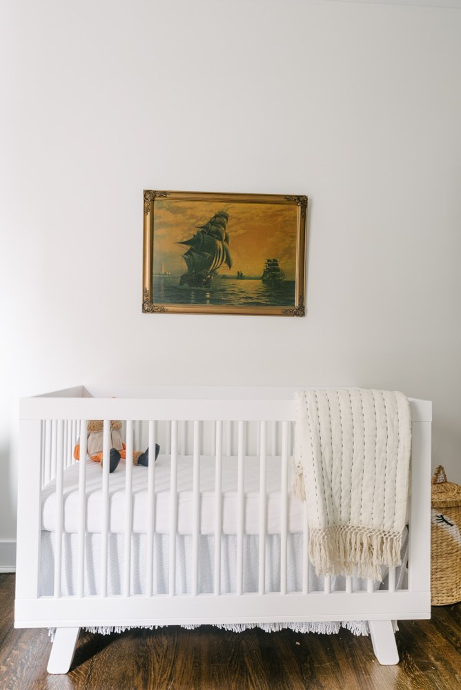 white crib with a painting above it