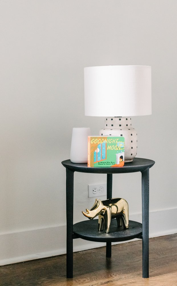 black side table with a white lamp, book and gold rhino figure on top