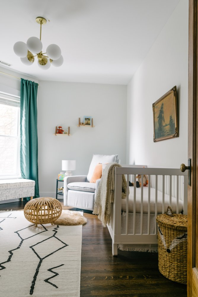 nursery with a crib, white rug and grey chair