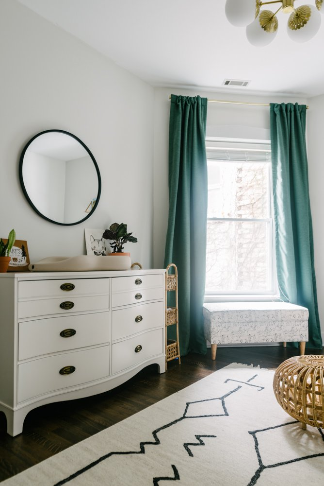 nursery room with drawers and green curtains