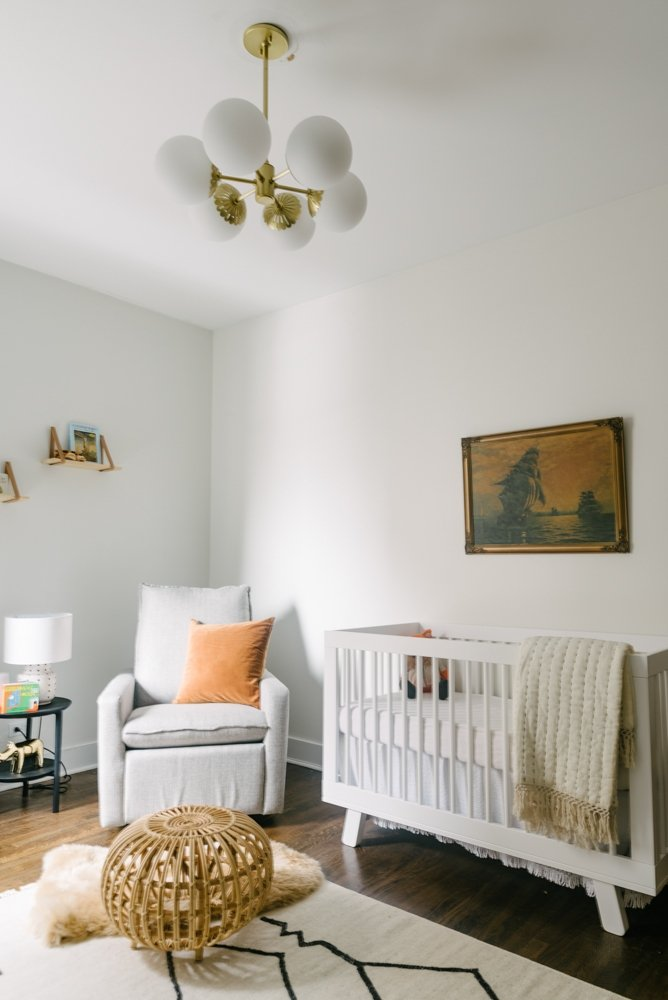 nursery room with a crib, chair, ottoman and ceiling light