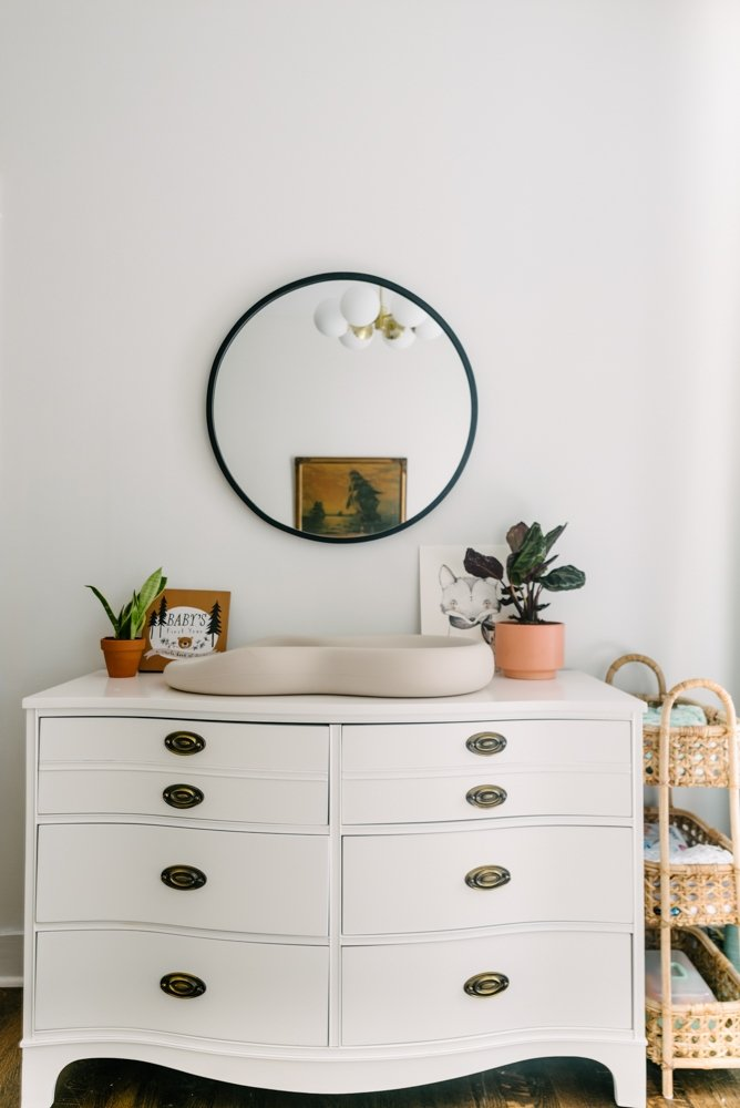 white dresser with a round mirror above it