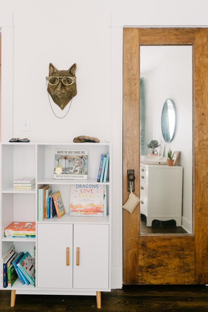 nursery with a white shelf and gold fox figurine on the wall