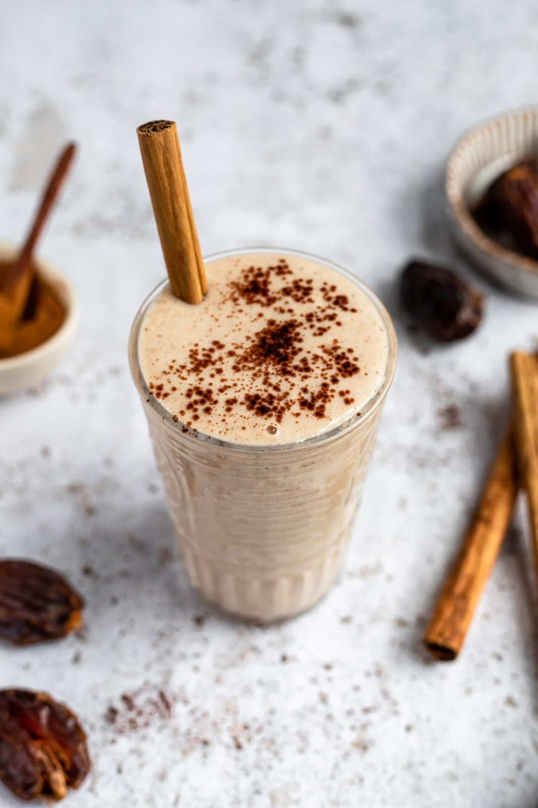 tahini date smoothie in a glass with a cinnamon stick