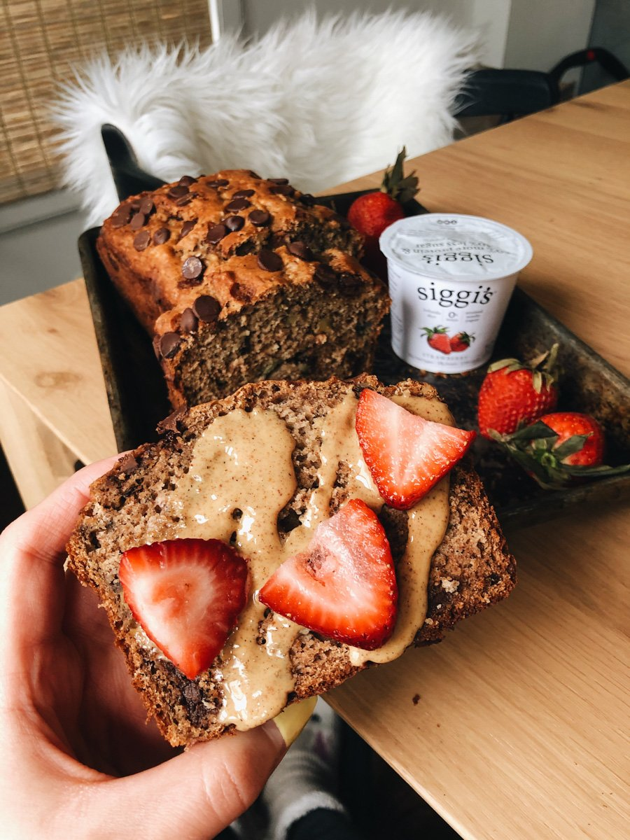 holding a piece of banana bread with strawberries on top