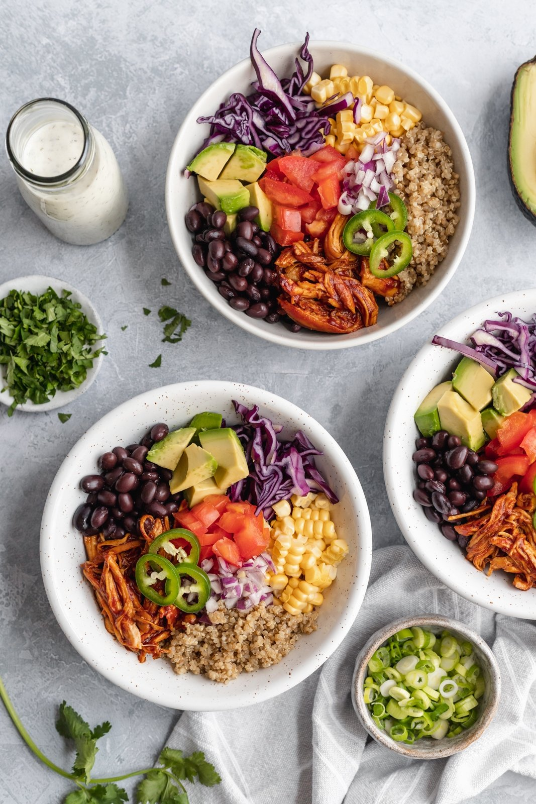 two healthy chicken quinoa bowls with beans, avocado, corn and cabbage