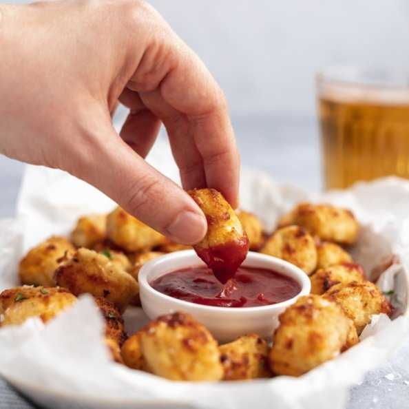 dipping a gluten free cauliflower tot in ketchup