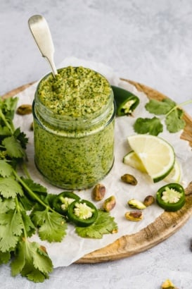 vegan cilantro pistachio pesto in a jar with a spoon