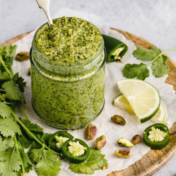 vegan cilantro pistachio pesto in a jar with a spoon