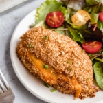 jalapeño popper stuffed chicken breast on a plate with a salad