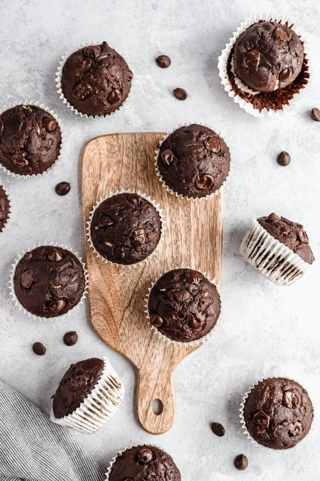 healthy chocolate banana zucchini muffins on a wooden board