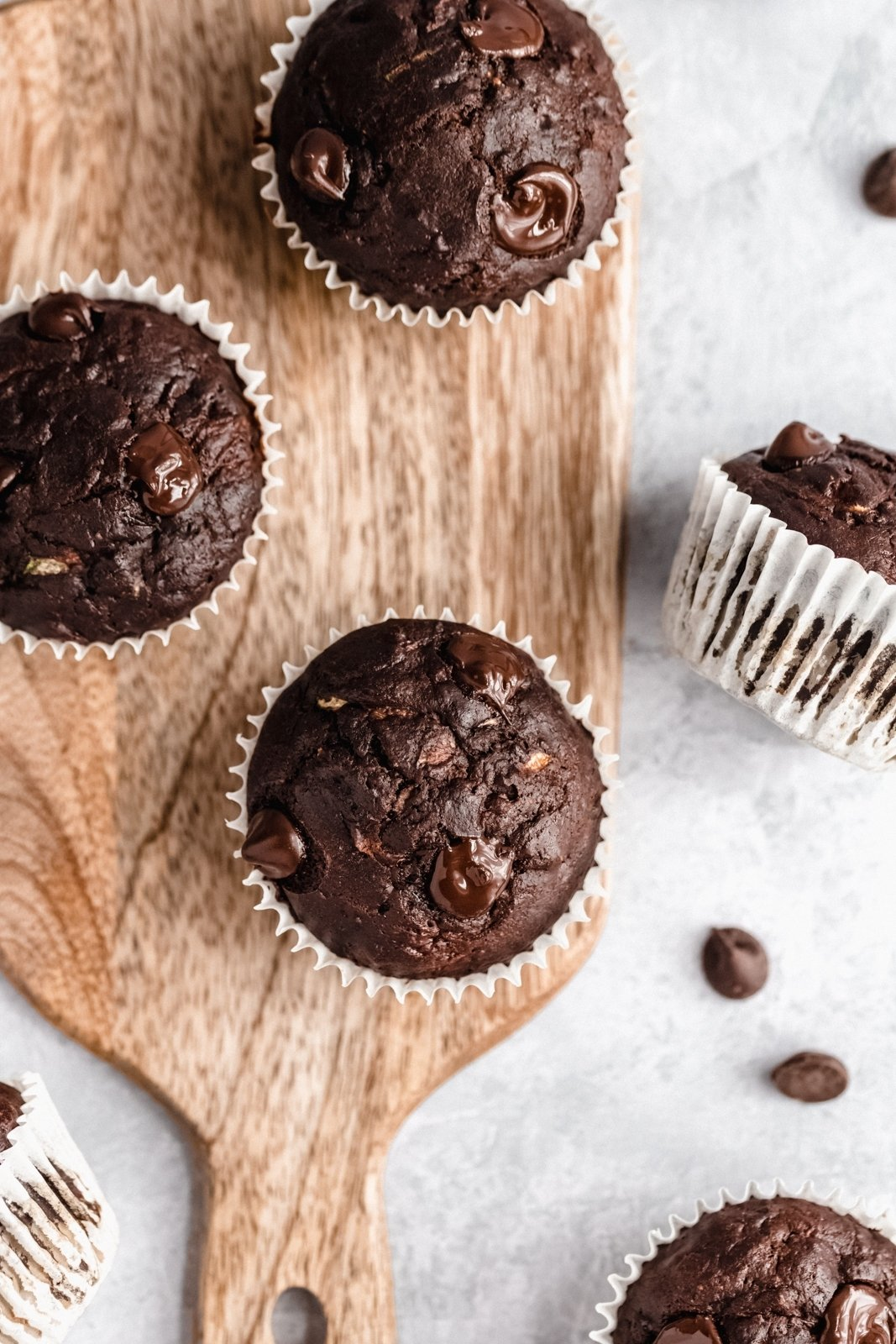 healthy chocolate zucchini muffins on a wooden board