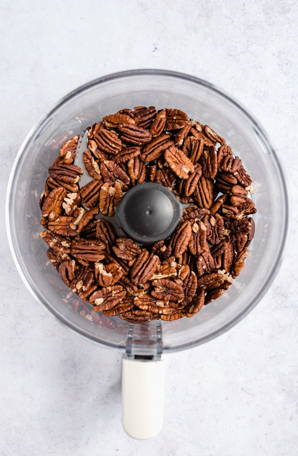toasted pecans in the bowl of a food processor