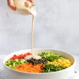 pouring homemade ranch salad dressing onto a salad