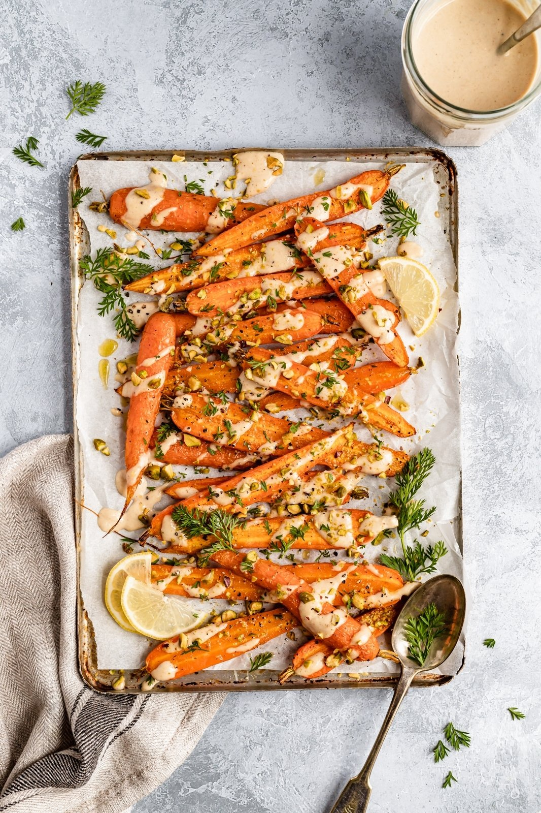 roasted carrots on a baking sheet drizzled with basic tahini sauce