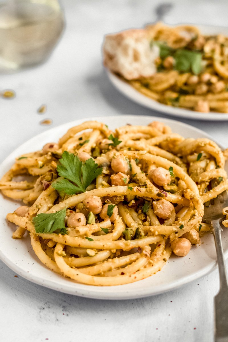 brown butter pistachio pesto pasta with chickpeas on a plate with a fork