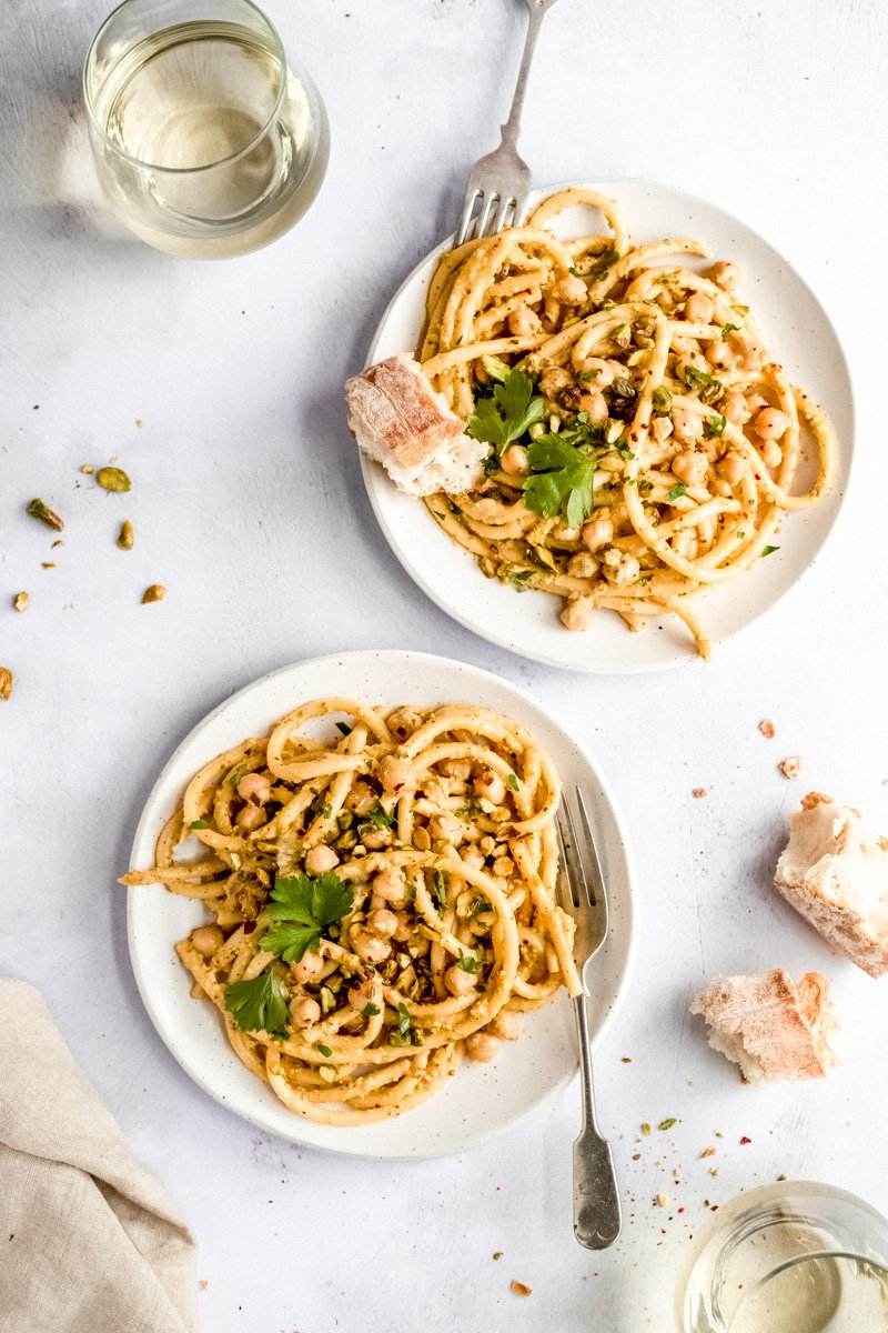 pistachio pasta with chickpeas on two plates with forks