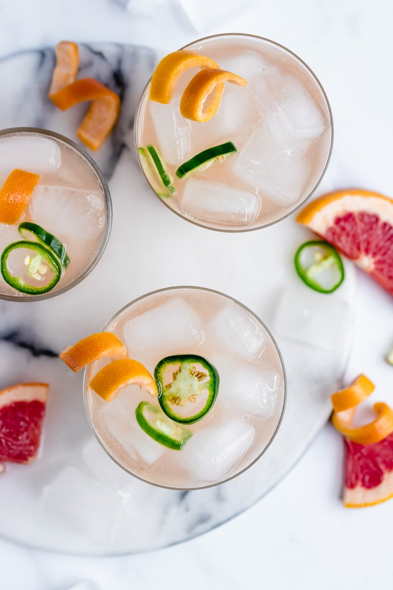 photo of three grapefruit cocktails on a marble surface