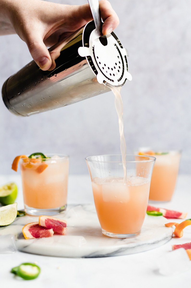cocktail shaker pouring grapefruit cocktail into a glass