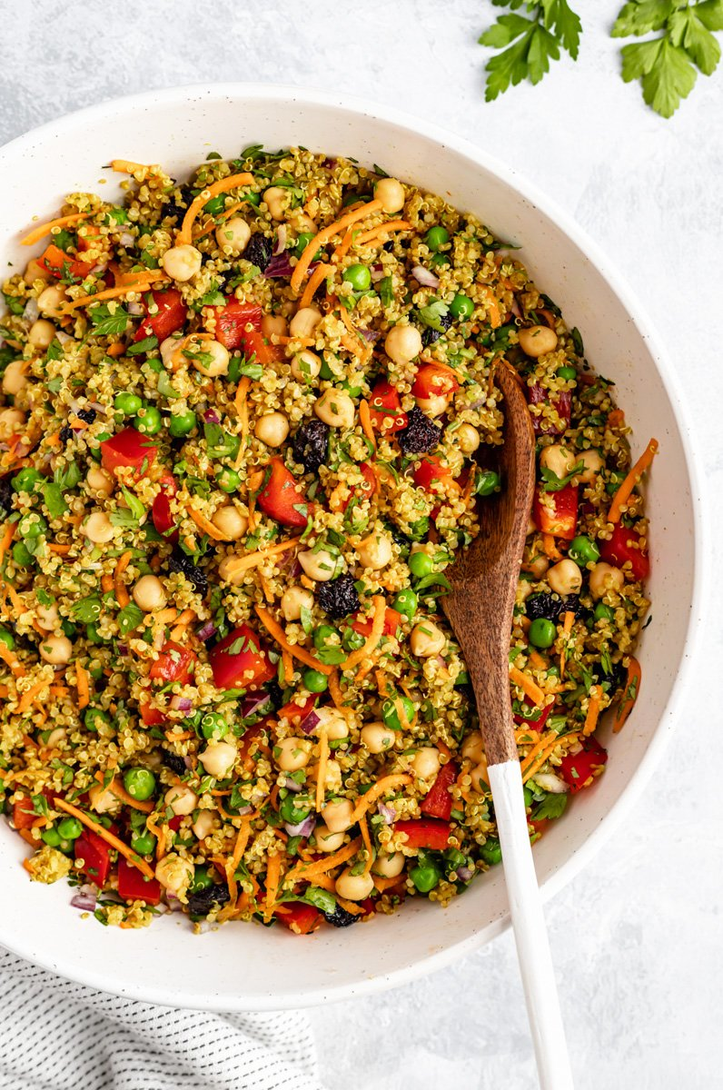 curry chickpea quinoa salad in a large bowl with a wooden spoon