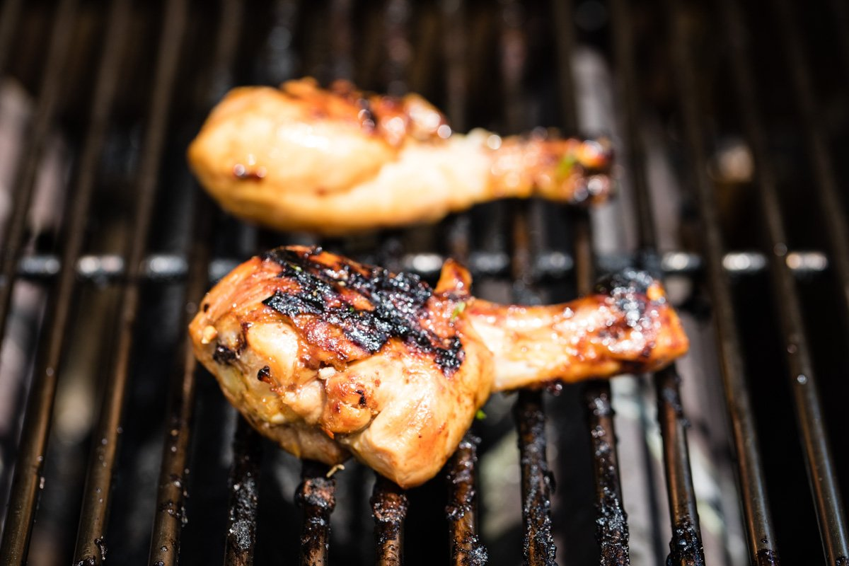 two grilled ginger chicken drumsticks on the grill