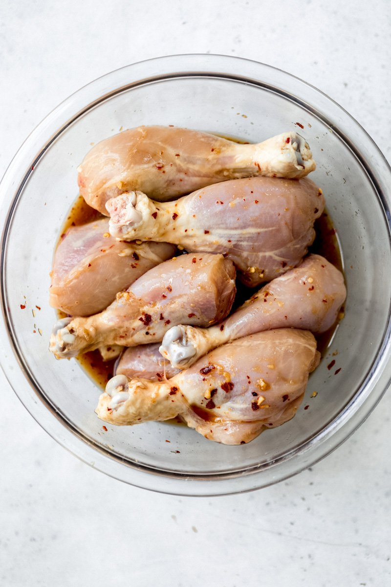 chicken drumsticks in a bowl with a marinade