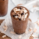 creamy vegan coconut chocolate zucchini smoothie in a glass topped with coconut