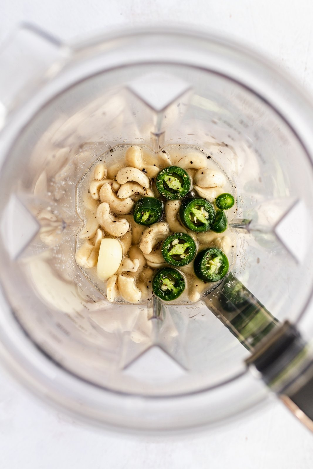 cashews and jalapeño slices in a blender
