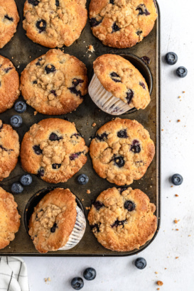 blueberry muffins with crumb topping in a muffin tin